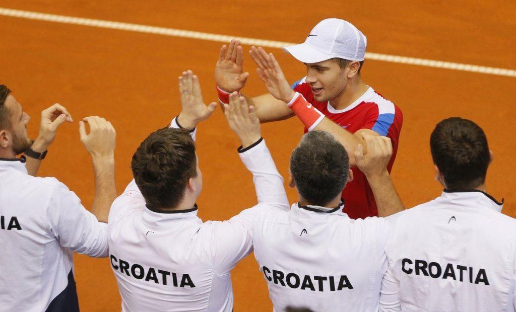 Coric celebra con su equipo la victoria contra Canadá